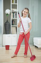 Portrait of a young girl sweeping floor with broom Stock Images