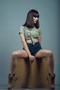 Portrait of young gorgeous dark-haired model wearing high waisted dark blue jeans shorts, khaki shirt and boots sitting on cube Royalty Free Stock Photo