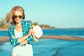 Portrait of young gorgeous suntanned blond wearing mirrored heart shaped sunglasses and checked blue shirt at the seaside