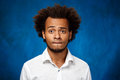 Portrait of young handsome african man over blue background. Royalty Free Stock Photo