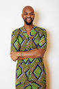 Portrait of young handsome african man wearing bright green national costume smiling gesturing Royalty Free Stock Photo
