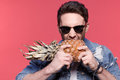 Portrait of young handsome casual man holding pineapple, Royalty Free Stock Photo