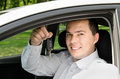 Portrait of young handsome man holding key in his own car outdoors Royalty Free Stock Images