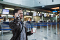 Portrait of young handsome man walking in modern airport terminal, talking smart phone, travelling with bag and coffee Royalty Free Stock Photo