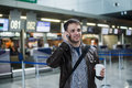 Portrait of young handsome man walking in modern airport terminal, talking smart phone, travelling with bag, wearing Royalty Free Stock Photo