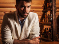 Portrait of young handsome man in white suit near home bar. Royalty Free Stock Photo