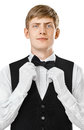 Portrait of young handsome waiter fixing his bow tie on a suit Royalty Free Stock Photo