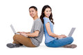 Portrait of young happy couple using laptop while sitting over white background Royalty Free Stock Images