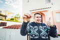 Portrait of a young happy man holding out new house key and gesturing thumbs up Royalty Free Stock Photo