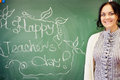 Portrait of young happy smiling teacher woman standing near chal photo chalkboard background with x s day phrase on it Royalty Free Stock Image