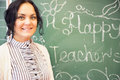 Portrait of young happy smiling teacher woman standing near chal photo chalkboard background with x s day phrase on it Stock Image
