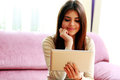 Portrait of a young happy smiling woman using tablet computer at home Royalty Free Stock Image