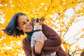 Portrait of young happy woman with little cute dog in park Royalty Free Stock Photo