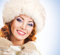 Portrait of a young and happy woman in a winter hat redhead posing the image is taken on light blue background Stock Image