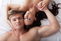 Portrait of young hugging lovers close up posing in bed Stock Images