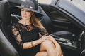 Portrait of a young lady in the car in a big black hat brunette with long hair wearing sun glasses wearing earrings ears is summer Royalty Free Stock Photo