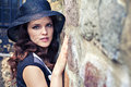 Portrait of young lady in hat near stone wall elegant woman black the old town Royalty Free Stock Photos
