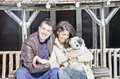 Portrait of a young love couple and their dog hugging in the winter mountain Royalty Free Stock Photo