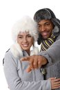 Portrait of young loving couple at wintertime interracial men pointing to the distance both smiling Royalty Free Stock Images