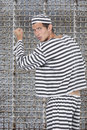 Portrait of young male prisoner in uniform standing against prison cell Royalty Free Stock Photo