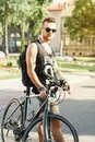 Portrait of a young man with a bicycle on the street. Black T-sh Royalty Free Stock Photo