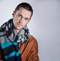 Portrait of young man in brown jacket with striped scarf over gray background close up studio shot Stock Photos