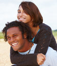 Portrait of a young man carrying young woman on hi Stock Image