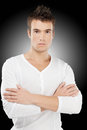 Portrait of young man courageous with crossed hands in white clothes on black background Royalty Free Stock Photo