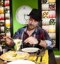 Portrait of a young man eating pizza the fashionable in hat eats in pizzeria Royalty Free Stock Images