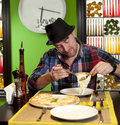 Portrait of a young man eating pizza the fashionable in hat eats in pizzeria Royalty Free Stock Photo