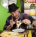 Portrait of a young man eating pizza the fashionable in hat eats in pizzeria Stock Photos