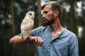 Portrait of young man in forest with owl in hand. Close-up. Royalty Free Stock Photo