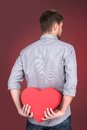 Portrait of young man holding heart shape over red background back view hiding his valentine gift Stock Photography