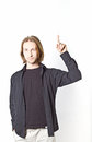 Portrait of young man with long blond hair pointing up on a white background Stock Photos