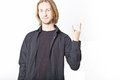 Portrait of young man with long blond hair rock n roll symbol on a white background Royalty Free Stock Image