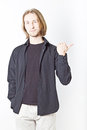 Portrait of young man with long blond hair showing direction to the left on a white background Royalty Free Stock Photo