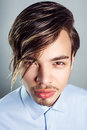 Portrait of young man with long fringe hairstyle on his eyes. studio shot. Royalty Free Stock Photo