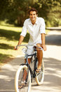 Portrait of young man riding old bicycle in park Stock Photo