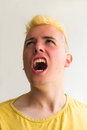 Portrait of young man screaming triumph with his mouth open a with yellow shirt Royalty Free Stock Images