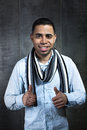 Portrait of a young man showing thumbs up in dark wall elegant latin smiling and two background grey Royalty Free Stock Photography