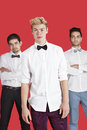 Portrait of a young man standing in front of male friends over red background men Royalty Free Stock Image