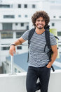 Portrait of young man standing on terrace happy wearing rucksack Stock Images