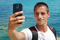 Portrait of young man taking selfie by cell, mobile phone , smartphone on beach near sea, ocean Royalty Free Stock Photo