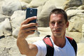 Portrait of young man taking selfie by cell, mobile phone , smartphone on on mountain Royalty Free Stock Photo