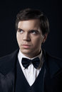 Portrait of young man in tuxedo isolated on dark Stock Photography