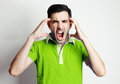 Portrait of young man wearing green shirt screamin screaming at camera grey background Stock Photo