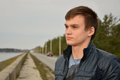 Portrait of the young man who is looking at the se sea a in a leather jacket standing near road and Stock Image