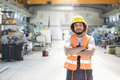 Portrait of young manual worker standing arms crossed in factory Royalty Free Stock Photo