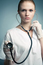 Portrait of young medical doctor woman with stethoscope a isolated over blue background copy space studio shot Stock Images