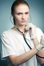 Portrait of young medical doctor woman with stethoscope a posing over blue background close up studio shot Stock Photo